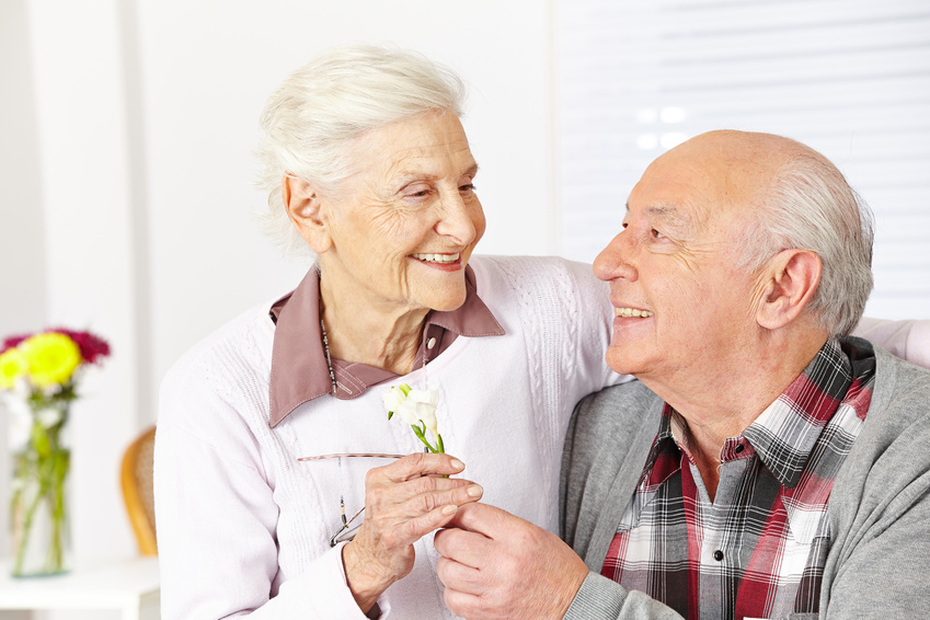 Senior schenkt einer lächelnden Seniorin eine Blume